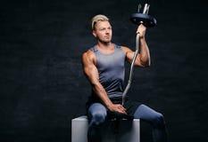 Hübscher, athletischer blonder Mann hält Barbell auf seiner Schulter Stockfotografie