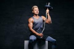 Hübscher, athletischer blonder Mann hält Barbell auf seiner Schulter Lizenzfreie Stockfotografie