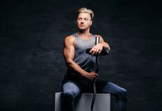 Hübscher, athletischer blonder Mann hält Barbell auf seiner Schulter Stockbilder