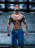 Hübscher athletischer junger Mann mit der Tätowierung, die oben schaut stockfoto