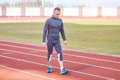 Hübscher athletischer Mann, der auf dem Tretmühlenstadion läuft stockfoto