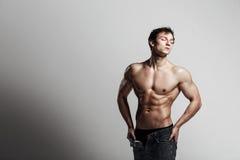 Hübscher athletischer Mann, der Seite in aufgeknöpften Jeans betrachtet Stron Lizenzfreies Stockbild