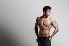 Hübscher athletischer Mann, der Seite in aufgeknöpften Jeans betrachtet Stron Stockfotos