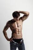 Hübscher athletischer Mann, der Seite in aufgeknöpften Jeans betrachtet Stron Lizenzfreie Stockbilder