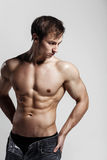 Hübscher athletischer Mann, der Seite in aufgeknöpften Jeans betrachtet Stron Lizenzfreie Stockfotografie