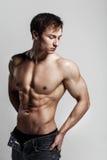 Hübscher athletischer Mann, der Seite in aufgeknöpften Jeans betrachtet Stron Lizenzfreie Stockfotos