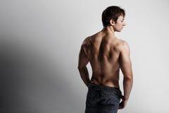 Hübscher athletischer Mann, der Seite in aufgeknöpften Jeans betrachtet Stron Stockfotografie