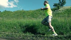 Hübscher athletischer Sportler, der gegen Hügel des grünen Grases läuft stock video footage