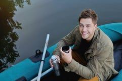 Hübscher attraktiver Mann auf dem Boot am See, Lebensstil Stockbilder