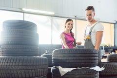 Hübscher Automechaniker, der einem Kunden hilft, von den verschiedenen Reifen zu wählen Stockbilder