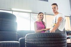 Hübscher Automechaniker, der einem Kunden hilft, von den verschiedenen Reifen zu wählen Stockfotografie