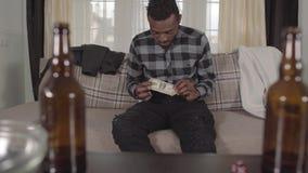 H?bscher b?rtiger Afroamerikanermann, der seine Tasche sitzt auf dem Sofa und findet nur einen Dollar ?berpr?ft Unscharfes leeres stock video