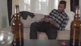 H?bscher b?rtiger Afroamerikanermann des Portr?ts, der seine Tasche sitzt auf dem Sofa und findet nur einen Dollar ?berpr?ft stock video