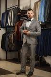 Hübscher bärtiger Geschäftsmann in der klassischen Klage Mann in der klassischen Weste gegen Reihe von Klagen im Shop Lizenzfreies Stockfoto
