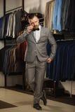 Hübscher bärtiger Geschäftsmann in der klassischen Klage Mann in der klassischen Weste gegen Reihe von Klagen im Shop Lizenzfreie Stockfotos