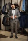 Hübscher bärtiger Geschäftsmann in der klassischen Klage Mann in der klassischen Weste gegen Reihe von Klagen im Shop Stockbilder