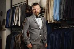 Hübscher bärtiger Geschäftsmann in der klassischen Klage Mann in der klassischen Weste gegen Reihe von Klagen im Shop Lizenzfreies Stockbild