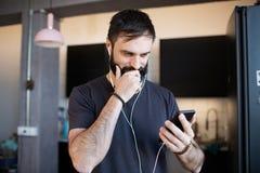 Hübscher bärtiger Kerl, der zufälliges graues T-Shirt hörende Musik in den Kopfhörern, soziale Netzwerke auf Smartphone überprüfe stockbild