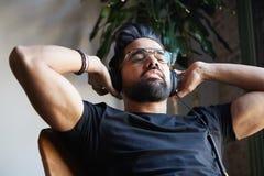 Hübscher bärtiger Mann in den Kopfhörern zu Hause hörend Musik Entspannungs- und Ruhezeitkonzept Unscharfer Hintergrund Lizenzfreie Stockfotografie