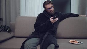 Hübscher bärtiger Mann, der auf Sofa sich entspannt stock footage