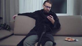 Hübscher bärtiger Mann, der auf Sofa sich entspannt stock video footage