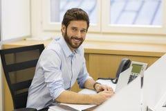 Hübscher bärtiger Mann, der im Büro auf Computer arbeitet Lizenzfreie Stockfotos