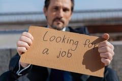 Hübscher bärtiger Mann, der Plakat in seinen Händen hält Stockfoto