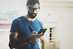 Hübscher bärtiger Mann, der Smartphonehände und Touch Screen des modernen Handys hält Unscharfer Hintergrund Blogger Stockfotografie