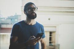 Hübscher bärtiger Mann, der Smartphonehände und Touch Screen des modernen Handys hält Unscharfer Hintergrund Blogger Stockbild