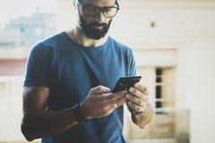 Hübscher bärtiger Mann, der Smartphonehände und Touch Screen des modernen Handys hält Unscharfer Hintergrund Blogger Stockbilder