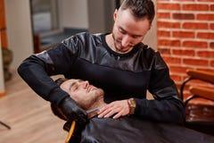 Hübscher bärtiger Mann erhält rasierte durch Friseur am Friseursalon Hintergrund mit Backsteinmauer Lizenzfreies Stockbild