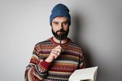 Hübscher bärtiger Mann im blauen Beanie denkend mit Stift und Notizbuch über Hintergrund stockfotos