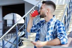 Hübscher bärtiger Mann mit Kopfhörern hörend Musik auf Stelle Lizenzfreie Stockfotografie