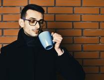 Hübscher bärtiger Mann mit Schale auf Backsteinmauerhintergrund lizenzfreies stockbild