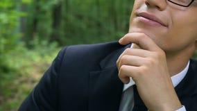 Hübscher Büroangestellter, der im Wald, freie Atmung, gute Klimaanlage sitzt stock video footage