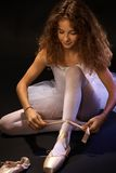 Hübscher Ballettstudent, der Spitze auf Schuh bindet Stockbilder