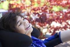 Hübscher behinderter Junge beim Rollstuhllächeln, oben schauend Stockbilder