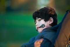 Hübscher behinderter Junge im Rollstuhl am Park, ruhiger Ausdruck Lizenzfreie Stockfotos