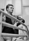 Hübscher blonder behaarter junger Mann auf Metallgeländer Stockbild