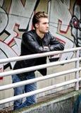 Hübscher blonder behaarter junger Mann auf Metallgeländer Lizenzfreie Stockbilder