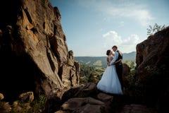 Hübscher blonder Bräutigam berührt leicht die Backe seiner reizend Braut bei der Stellung auf den sonnigen Felsen Stockfotografie