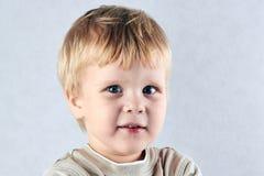 Hübscher blonder Junge, der Kamera betrachtet Stockfotografie