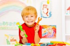 Hübscher blonder Junge mit Schlüssel im Klassenzimmer Stockfotografie