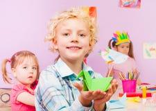 Hübscher blonder Junge zeigt Origami im Klassenzimmer Stockfotografie