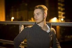 Hübscher blonder junger Mann allein in der städtischen Landschaft Stockbild