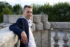 Hübscher blonder junger Mann auf Marmorgeländerdocke Lizenzfreies Stockfoto