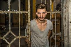 Hübscher blonder junger Mann, der alte Tür öffnet Lizenzfreies Stockfoto