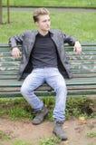 Hübscher blonder junger Mann, der auf Parkbank sitzt Stockbild