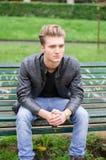 Hübscher blonder junger Mann, der auf Parkbank sitzt Lizenzfreie Stockfotos