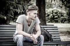 Hübscher blonder junger Mann, der auf Parkbank sitzt Lizenzfreie Stockbilder